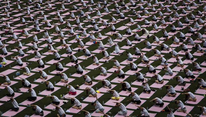 Chinese studenten nemen deel aan een workshop ter ere van de Internationale Dag van de Yoga op 21 juni 2015 in Beijing, China. Foto: Kevin Frayer / Getty