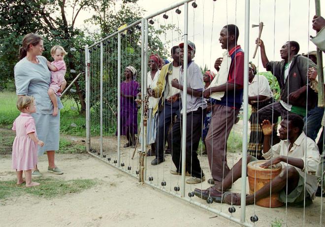 Pippa van Rechteren staat met haar tweeling bij het hek van haar land. Een groep Zimbabwanen zonder land wil binnenkomen. Foto: Str Old / Reuters