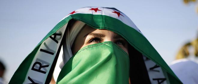 """Een Syrische vrouw, die in Jordanië leeft, draagt de vlag van de Syrische oppositie als hoofddoek tijdens een demonstratie in Amman op 21 augustus, 2014. Op de doek staat het woord """"Syria"""". Deze vrouw demonstreert weliswaar voor vrede in Syrië, maar is niet een van de vijf geïnterviewden. Foto: Muhammad Hammad / Reuters"""
