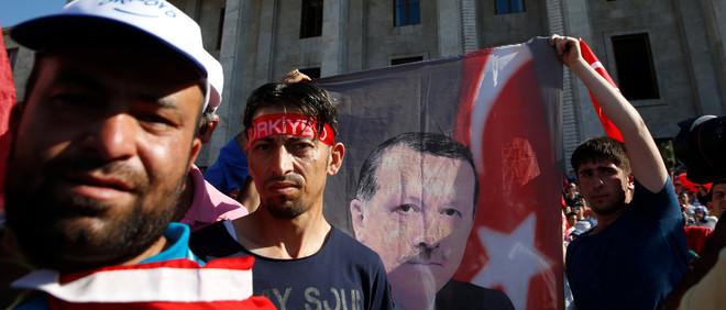Supporters van de Turkse president Recep Tayyip Erdogan houden zijn portret omhoog voor een parlementsgebouw in Ankara. Foto: Baz Ratner / Reuters