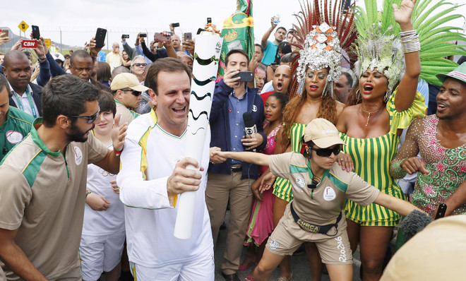 De burgemeester van Rio de Janeiro draagt het Olympisch vuur naar het Maracanã-stadion. Betogers hebben geprobeerd met een plens water het vuur te doven uit protest tegen de miljarden die Brazilië besteedde aan de Olympische Spelen. Foto: Getty