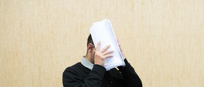 Een verdachte komt de rechtszaal binnen met papieren voor zijn hoofd op 7 juli, 2016. De eerste twee verdachten van aanranding tijdens nieuwjaarsnacht in Keulen moeten voorkomen. Foto: Marius Becker / DPA
