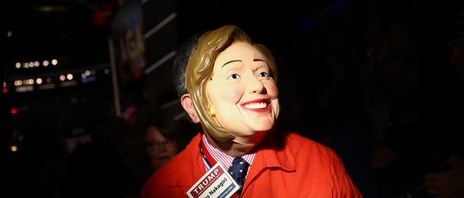 Een bezoeker van de Republikeinse conventie in Cleveland draagt een Hillary Clintonmasker en een gevangene-outfit op 21 juli, 2016. Foto: Andrew Harrer / Bloomberg / Getty Images