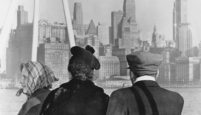 Een Duitse immigrantenfamilie kijkt uit over de Skyline van New York. Ze zijn met de S.S. Nieuw Amsterdam naar Amerika gevaren om een nieuw bestaan op te bouwen. Foto: Getty