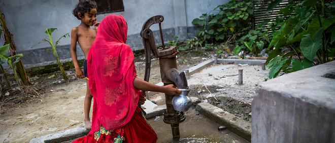 Een jonge vrouw tapt drinkwater uit een put die door de Universiteit van Columbia is aangelegd en gecontroleerd. Foto: Dominic Blewett
