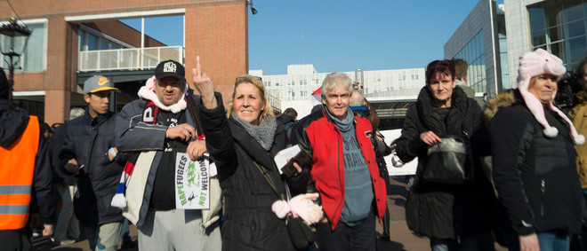 Pegida-demonstratie bij de Stopera in Amsterdam op 27 februari 2016. Op de foto staan aanhangers van Pegida. Zij richten zich naar de overkant van het water. Daar staan tegendemonstranten van o.a. AFA. Foto: Oscar Brak
