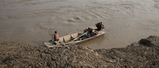 Lokale vissers in een boot op de Yellow River in Sanmenxia, China. Er zit veel vis in de modder nadat de Sanmenxiadam open heeft gestaan om ruimte te geven aan het extra water. Foto:  Jie Zhao / Corbis via Getty Images