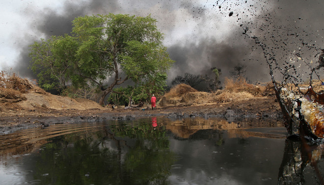 Een man loopt langs een olielek bij de pijpleiding in Dadabili op 2 april 2011, Nigeria. Foto: Afolabi Sotunde / Reuters