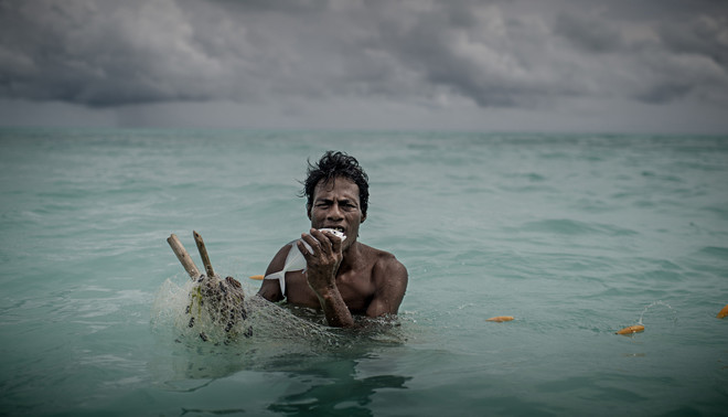 Een visser in Kiribati bijt een door hem gevangen vis dood. Kiribati heeft een gele kaart gekregen van de EU. Foto: Jonas Gratzer / LightRocket via Getty Images