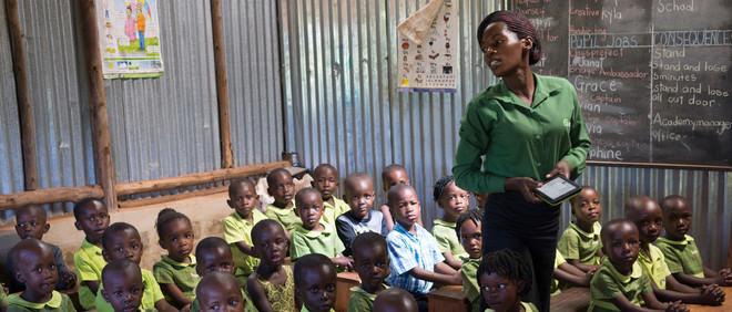 Een docent staat voor de klas op een basisschool van Bridge International Academies in Mpigi, Oeganda. Foto: Jon Rosenthal / Alamy