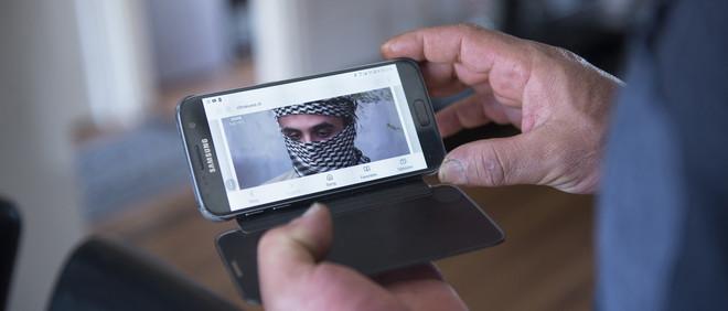 Mohamed laat een interview met zijn zoon Reda zien op zijn  telefoon. Foto: Els Zweerink (voor De Correspondent)