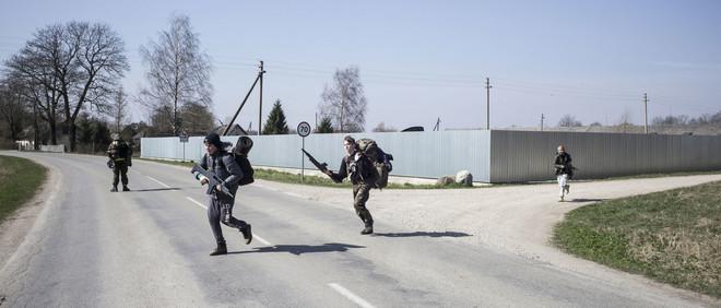 Jonge leden van Litouwse Schuttersvereniging rennen over de weg op het Litouwse platteland. Foto: Tomaso Clavarino