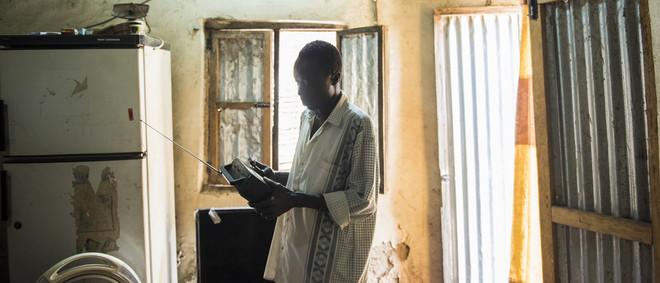 Charles Lomodong zocht Soedanese radioluisteraars op. Dit is Thomas Ali, terwijl hij via de radio een nieuwsuitzending volgt. Juba, Zuid-Soedan. Foto: Charles Lomodong (voor De Correspondent)