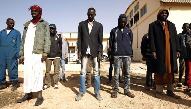 Illegale migranten voor het Qanfouda detentie centrum in een buitenwijk van Benghazi, voordat ze worden terug gestuurd naar het land van herkomst, 2 december 2017. Foto: Abdullah Doma / ANP