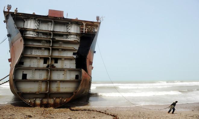 Een Pakistaanse arbeider trekt aan een touw dat vastzit aan de buitenste laag van een illegaal gedumpt schip, Pakistan, 2012. Vijftig werknemers zijn zo'n 3 maanden bezig om een schip van 40.000 ton af te breken. Foto: Roberto Schmidt / AFP