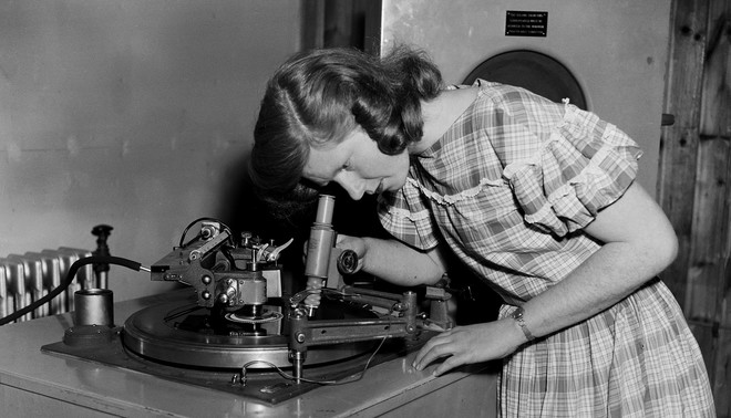 Student Jean Cooke onderzoekt de groeven van een plaat die ze zojuist heeft gesneden bij BBC Engineering Training Department, Worcestershire,1956. Foto: John Franks / Getty