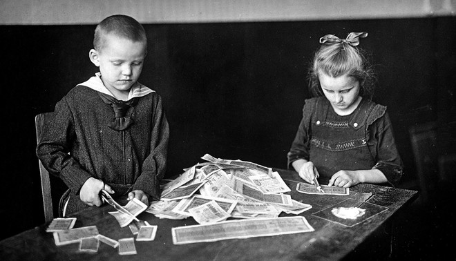 Kinderen knutselen met geld. Foto: Albert Harlingue / Getty