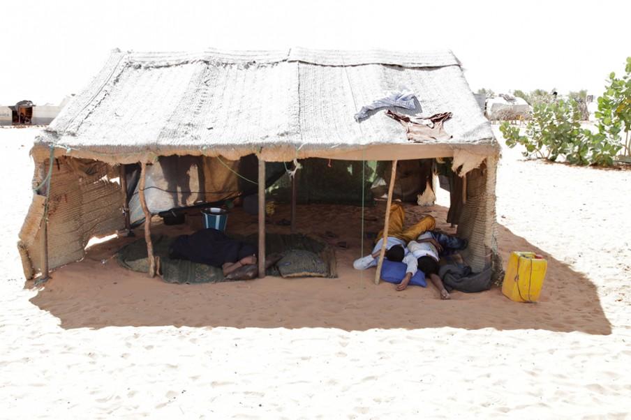 Een gevluchte familie rust tussen de middag in de schaduw van hun tent. Overdag kan de temperatuur oplopen tot 50 graden Celsius. Foto: Andreas Stahl