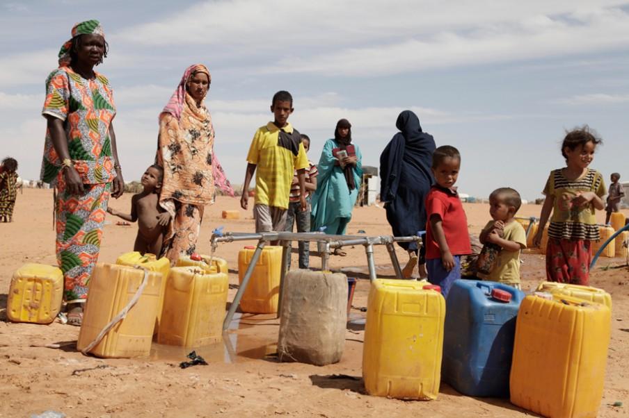 Vrouwen en kinderen vullen tanks met drinkwater bij een van de waterbronnen in M'Bera. Foto: Andreas Stahl