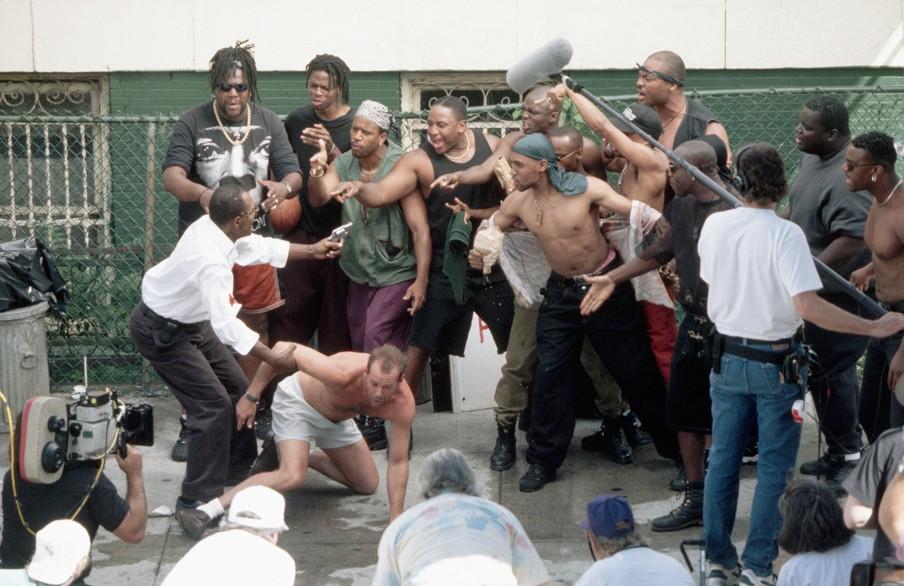 De context van de foto boven dit verhaal: de set tijdens de opnames van de film 'Die Hard with a Vengeance'. In de film draagt Bruce Willis het bord 'I Hate Niggers' in Harlem om een aanslag ergens anders in de stad New York te voorkomen. Foto: HH