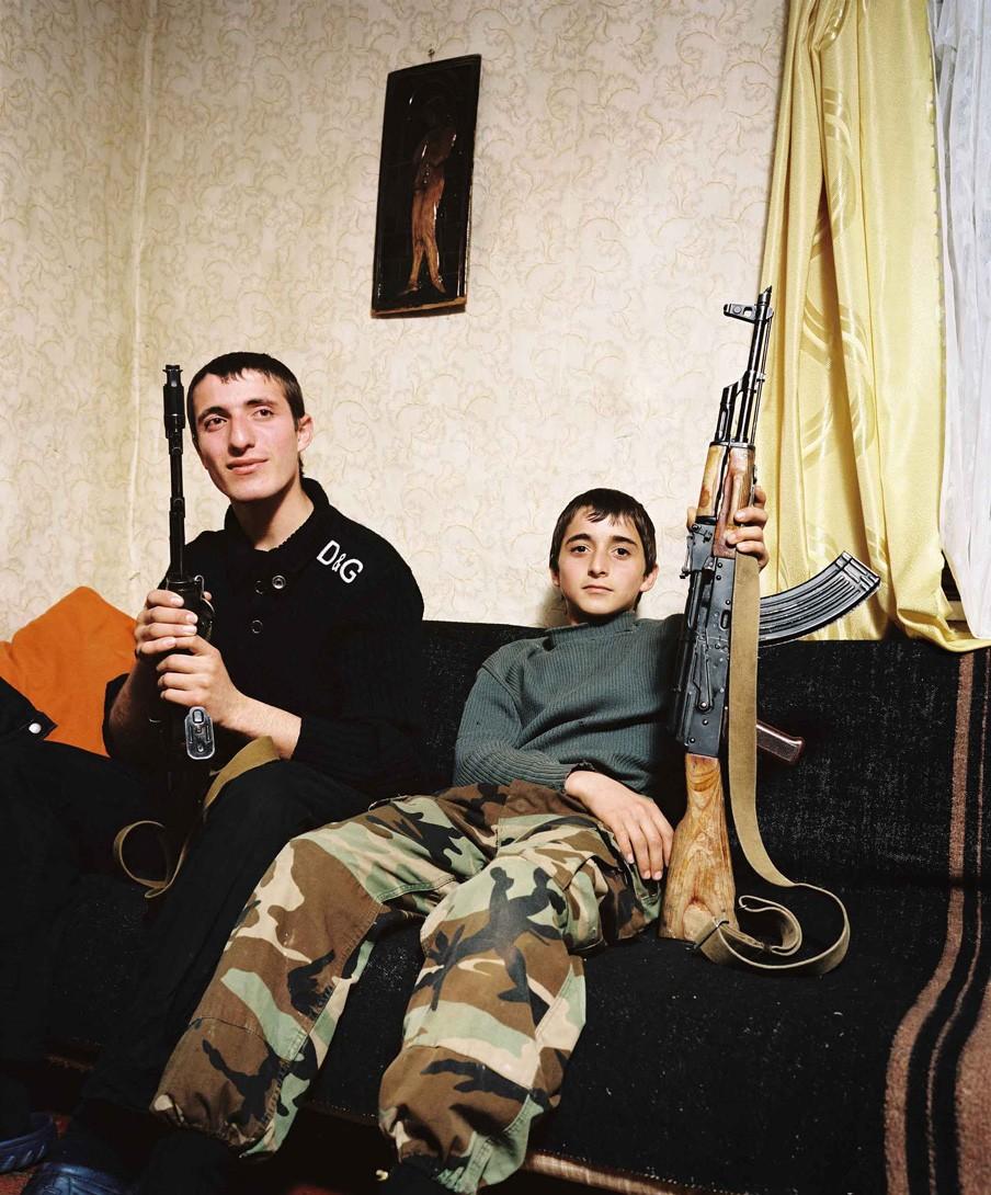 De broers Zashrikwa (17) en Edrese (14) zitten vol trots met een Kalasjnikov op de bank in het huis van hun oom en tante. Ze wonen in een afgelegen berggebied op de grens van Abchazië en Georgië. Foto: Rob Hornstra/Flatland Gallery