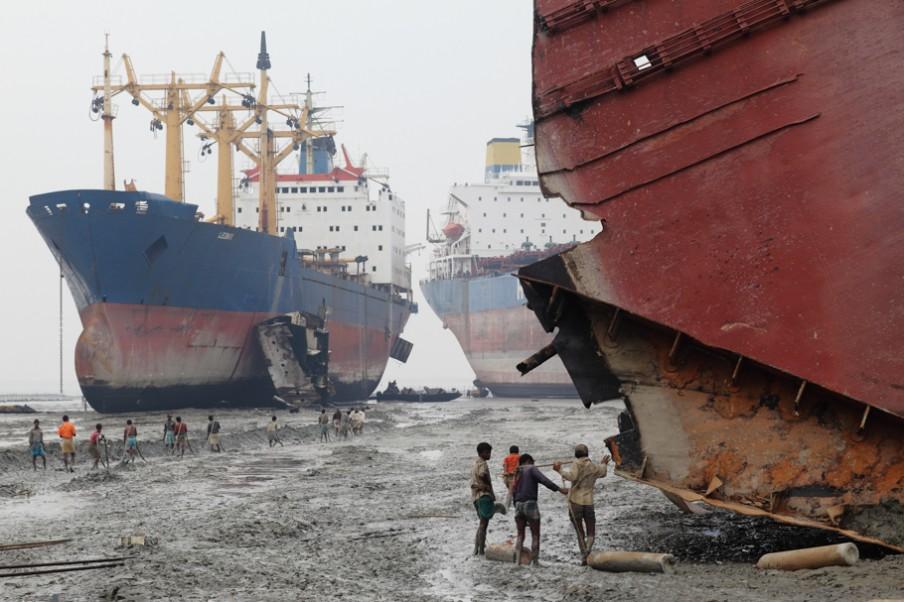 De werkers links in beeld trekken met stalen kabels onderdelen van schepen dichter bij de kust om het daar verder te demonteren. Rechts in beeld sjouwen mannen gasflessen naar het schip om met gasbranders het staal te kunnen snijden. Foto: Pierre Torset