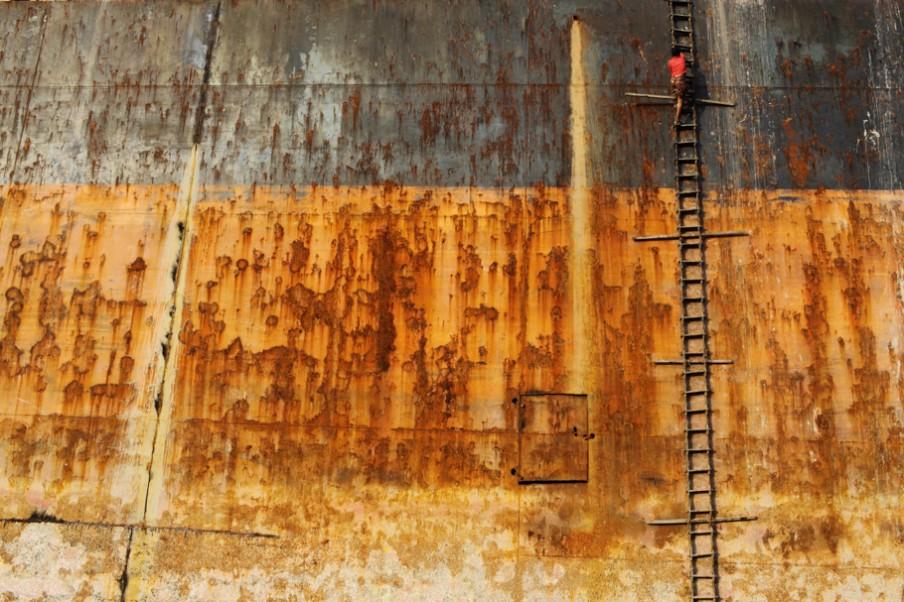 Via handgemaakte trappen klimmen sloopwerkers op de containerschepen en olietankers. Het vallen van schepen is de op een na belangrijkste doodsoorzaak in deze industrie (Chittagong in Bangladesh). Foto: Pierre Torset