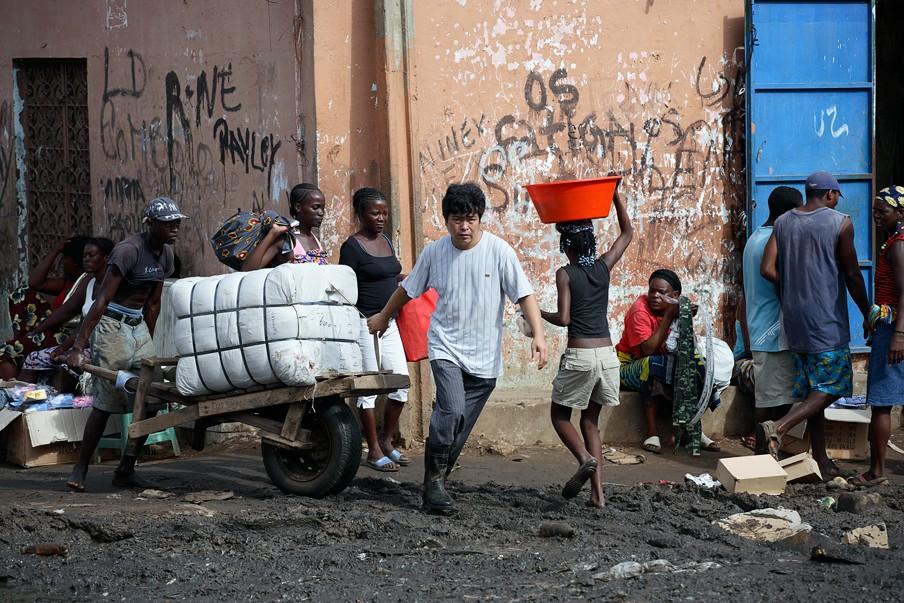 Een Chinese zakenman vervoert, samen met zijn werknemer, goederen die zijn overgevolgen uit China. In de Angolese stad Luanda wonen veel Chinezen. Foto: Per-Anders Pettersson/Getty Images