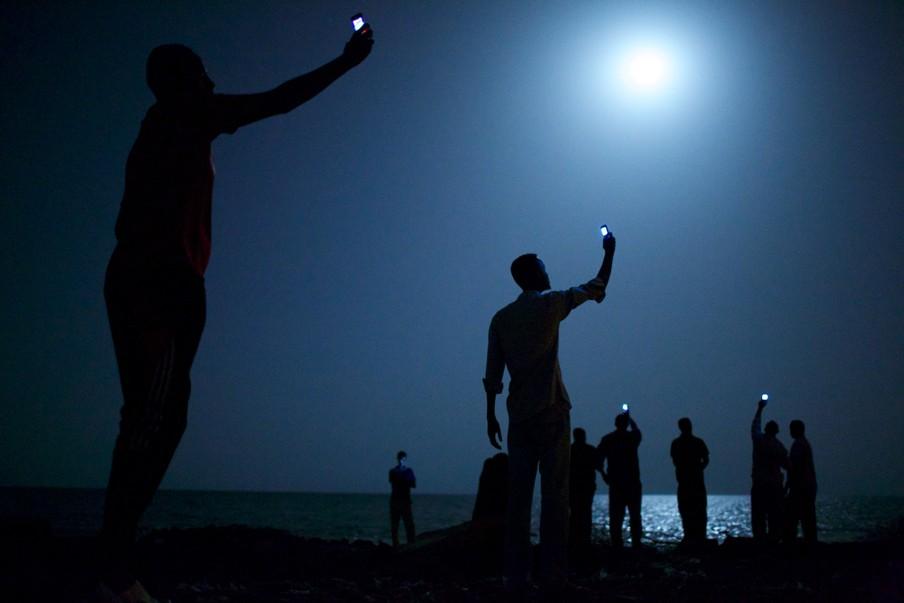 Afrikaanse migranten aan de kust van Djibouti steken telefoons in de lucht in de hoop het telefoonsignaal van buurland Somalië op te vangen om zo contact te krijgen met familie in het buitenland. Foto: John Stanmeyer (VII for National Geographic)