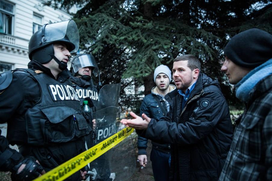 Demonstranten discussiëren met de politie die hen de weg verspert naar het gemeentehuis dat tijdens eerdere protesten in de brand was gestoken. Foto: Jodi Hilton