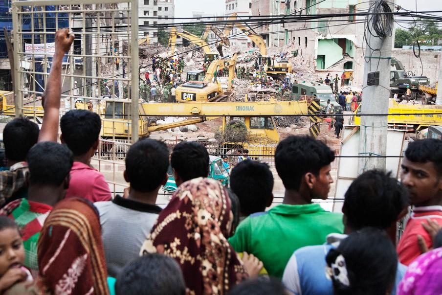 Twee weken na de instorting van het gebouw waarin ook Rana Plaza gevestigd was, staan mensen nog steeds te wachten bij de opruimwerkzaamheden in de hoop dat familieleden nog onder het puin vandaan zullen komen. Foto: Pieter van den Boogert