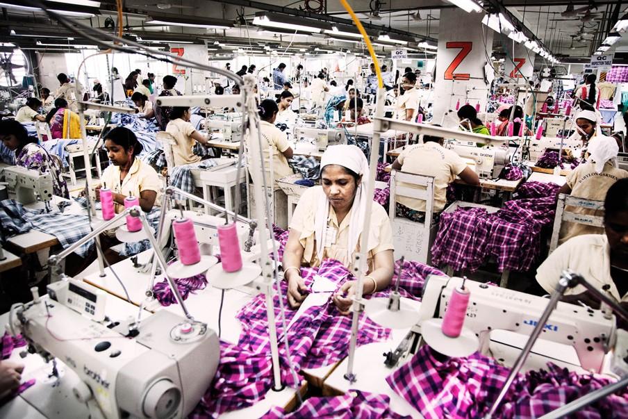 De textielfabriek Babylon Group in Dhaka. Alle arbeiders werken aan hetzelfde kledingstuk. Iedere rij arbeiders werkt aan een ander onderdeel, aan het einde wordt alles aan elkaar gezet. Foto: Pieter van den Boogert