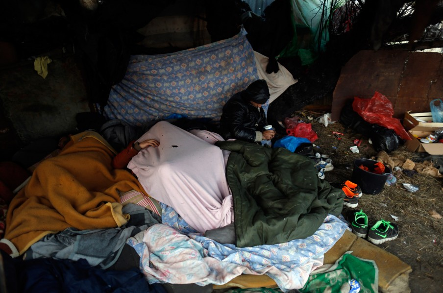 Migranten rusten in een verlaten fabriek vlakbij Subotica. Foto: Darko Vojinovic/HH