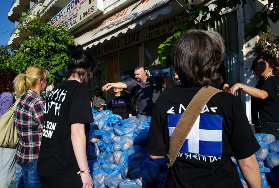 9 november 2013: Parlementslid Ilias Panagiotaros (midden) deelt voedsel uit aan Grieken, op vertoon van hun paspoort. Foto: Maro Kouri