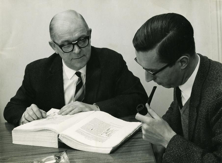 Nico Schimmel poseert al lezend samen met een collega van het NRP. Foto: privéarchief