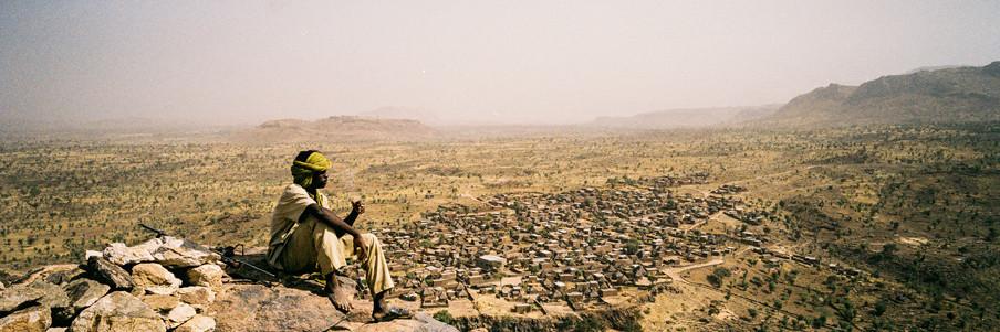Boven: een oase. Onder: een soldaat van het Soedanese regeringsleger rookt een sigaret terwijl hij uitkijkt over het gebied dat in handen is van de rebellen. Foto's: Adriane Ohanesian