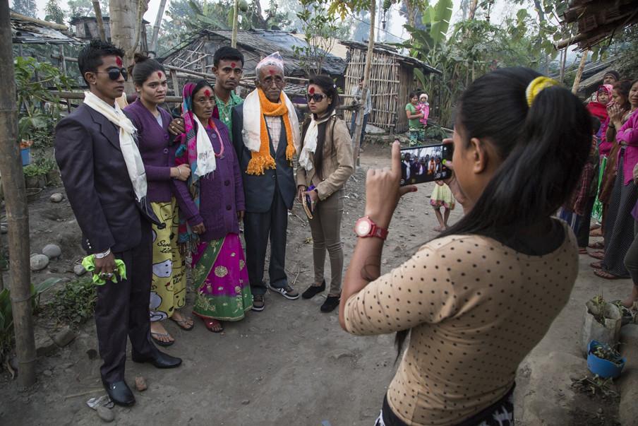 Familieleden gaan met elkaar op de foto vlak voordat een deel van de familie uit het vluchtelingenkamp in Oost-Nepal naar de Verenigde Staten zal vertrekken.