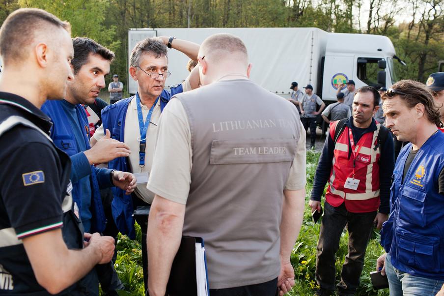 Teamleider van het EU coördinatieteam Frieder Kircher (hand in het haar) overlegt met de Litouwse teamleider Gediminas Suksta (in grijs) bij de grens van Modexland. Foto: Pieter van den Boogert