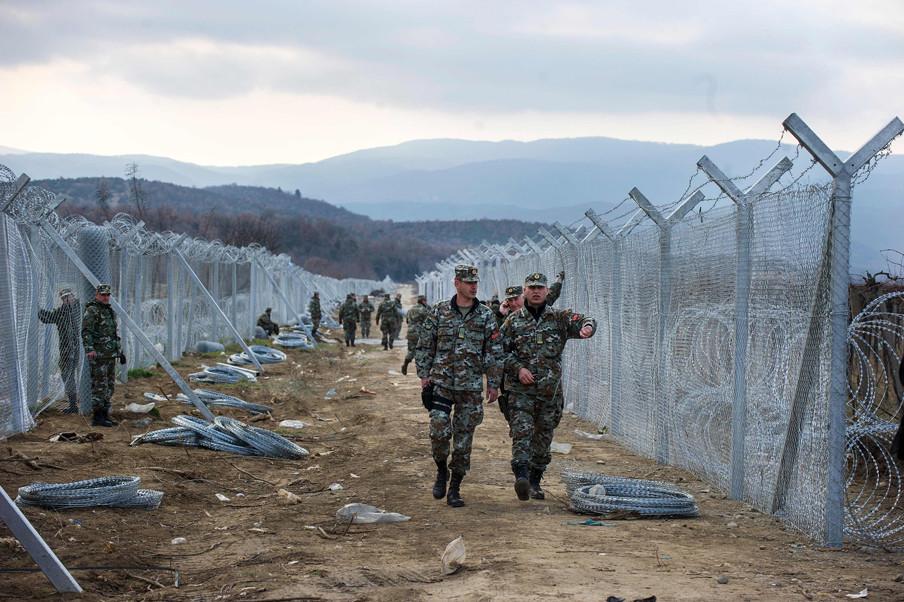 8 februari 2016: Militairen installeren een hek op de grens tussen Macedonië en Griekenland. Foto: Robert Atanasovski / AFP