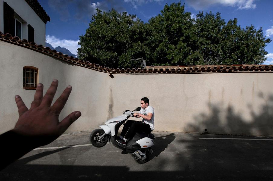 Een jongen maakt een wheelie op een scooter, iets wat grappend ook wel de nationale sport van Marseille wordt genoemd. Foto: Bharat Choudhary