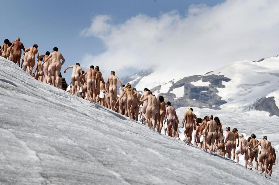 Naakte vrijwilligers poseren voor de Amerikaanse fotograaf Spencer Tunick op de ijskoude Zwitserse gletsjer Aletsch. Dit is de making-of  van een Greenpeace-campagne over de opwarming van de aarde. Foto: Fabrice Coffrini / AFP