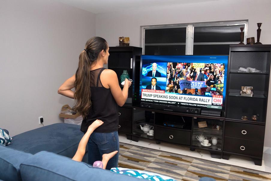 Hany kijkt op televisie naar een toespraak van Trump. Foto: Eline van Nes