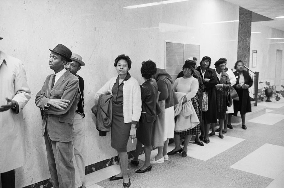 Mensen staan in de rij om zich in te schrijven om te kunnen stemmen. Martin Luther King staat links achter de man in pak tegen de muur geleund, later op de dag wordt hij door de politie uit de rij gehaald. Selma, 1965. Foto: Getty