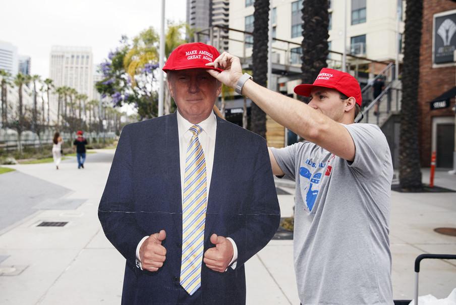 Een verkoper zet een 'Make America great again'-pet op een uit karton gesneden Donald Trump. Foto: Patrick T. Fallon / Bloomberg via Getty Images