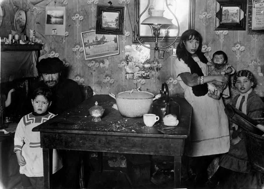 Huurwoning in de Jodenbuurt. De gemeente verhuurt de woning voor een gulden in de week. Een vader met zijn kinderen rond de tafel waarop een pan, een ketel en enkele stuks serviesgoed staan. Foto: Spaarnestad / Hollandse Hoogte
