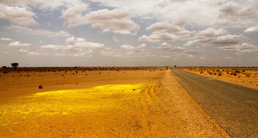 De mijnen aan de horizon en zwavelkorrels langs de weg naar Niamey. Foto's: Lucas Destrijcker
