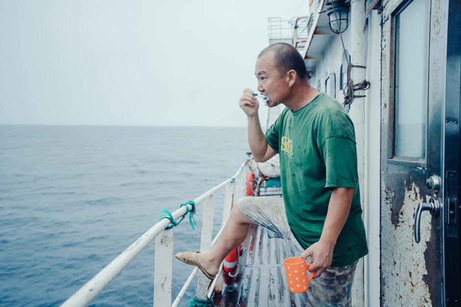 Turbine-ingenieur Jin poetst zijn tanden op het dek. Foto: Liu Yuyang / Greenpeace
