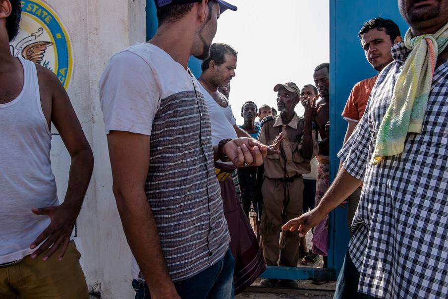 Mei 2015: Jemenitische vluchtelingen (voorgrond), een bewaker (midden) en Ethiopische vluchtelingen (achtergrond) bij het deportatiecentrum van het IOM in Obock, Djibouti. Alleen de Jemenieten mogen naar buiten.