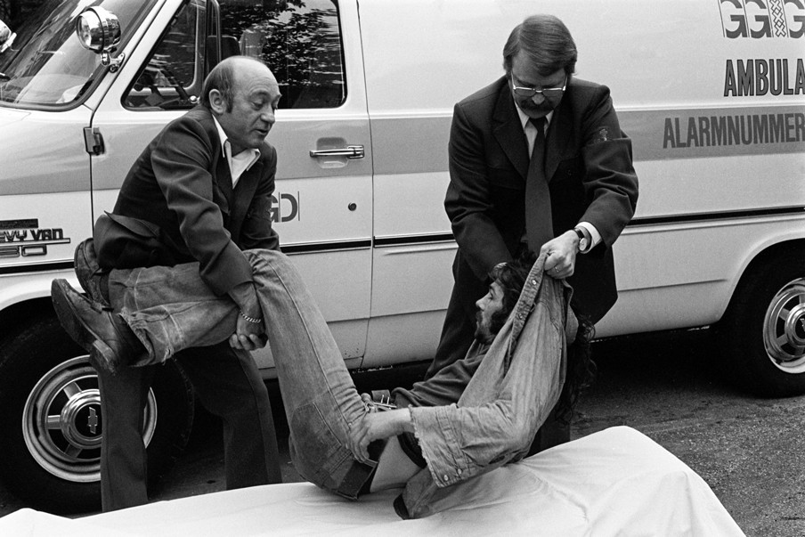 Een heroïneverslaafde op straat in Amsterdam wordt door een ambulance meegenomen, september 1985. Foto's: Sabine Joosten / Hollandse Hoogte