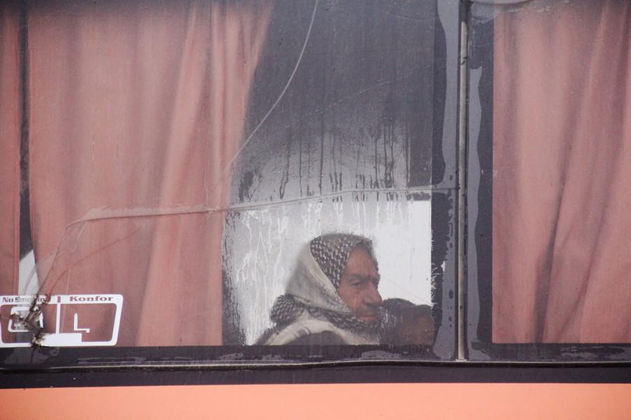 Syriërs zitten aan boord van een bus die vanuit Fuaa en Kafraya mensen naar Rashidin evacueert op 14 april, 2017. Foto: Omar Haj Kadour / AFP / ANP